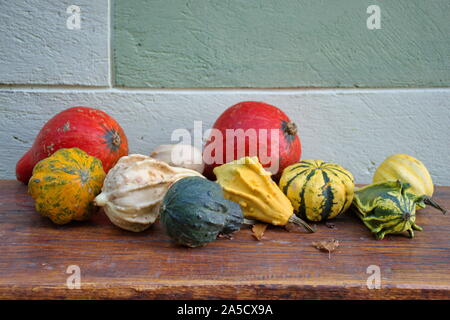Closeup of colorful pumpkins on the wooden table outside the house - Stock Photo
