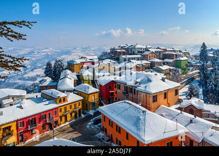 View from above of colorful houses of small italian town covered in snow in Piedmont, Northern Italy. - Stock Photo