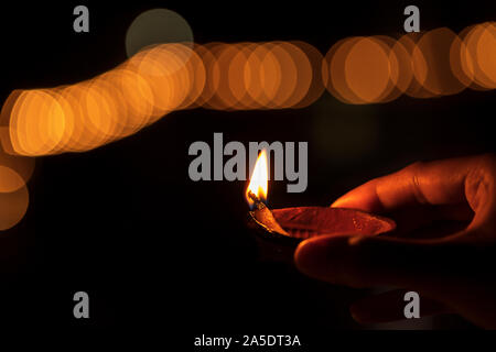 Diwali or deepawali photo with woman or female holding oil lamp or diya during festival of light with space for text isolated on black background. - Stock Photo