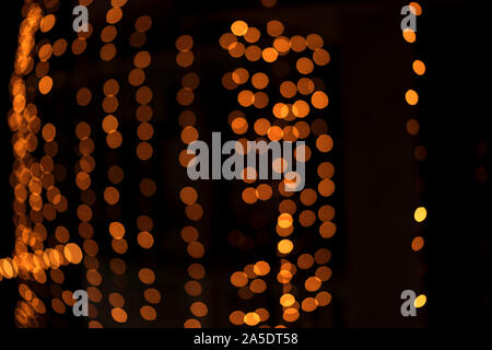 Abstract blurred bright yellow orange vintage lights bokeh background defocused isolated in Black. Concept for Diwali, greetings card, festive season, - Stock Photo