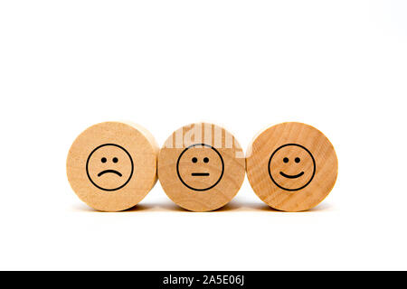 Smiley review. Happy, neutral and frown face on round wood blocks - Stock Photo