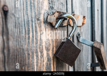 An open padlock hanging on the gate of an old village barn - Stock Photo
