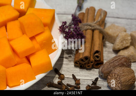 Chopped pumpkin on white plate with cinnamon sticks, anise star, nutmeg and cloves on grey wooden table background. Ingredients for baking tasty pie o - Stock Photo