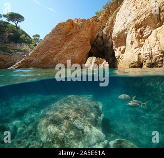 Rocky coast with natural arch, split view over and under water, Mediterranean sea, Spain, Costa Brava, Catalonia, Palamos, Cala Foradada