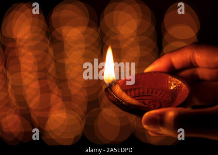 Happy Diwali - Female hand holding Diya clay oil lamp at night, temple with bokeh light. Stock background image for festive decoration, rituals. - Stock Photo