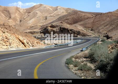 curvy sandy road on a highway that runs along the Dead Sea from one side and Edom Mountains at Arava Desert from the other in Israel. - Stock Photo