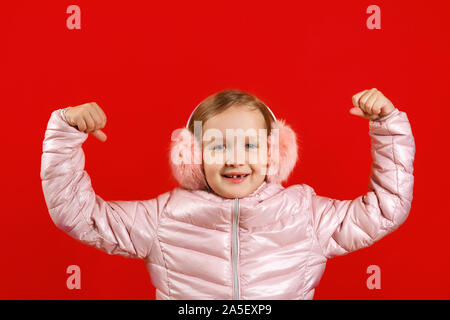 Little girl shows strong hands. A child in a jacket and warm ear muffs on a red background. The concept of education, school, success, power, feminism - Stock Photo
