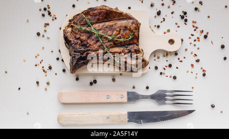 Appetizing medium rar grilled t-bone steak on a wooden cutting board on a light background with spices. Horizontal shot - Stock Photo
