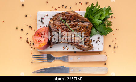 Food banner: medium rare grilled t-bone steak with spices and herbs on a wooden cutting board on a light background - Stock Photo