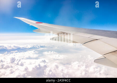 Narita, Japan - March 27, 2019: View of airplane wing through window of flight above clouds with blue sky and red circle national Japanese symbol - Stock Photo