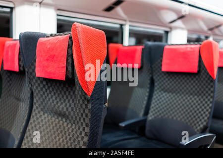 Empty red comfortable chairs seats row in aisle in subway train interior inside with nobody and modern comfy seating - Stock Photo