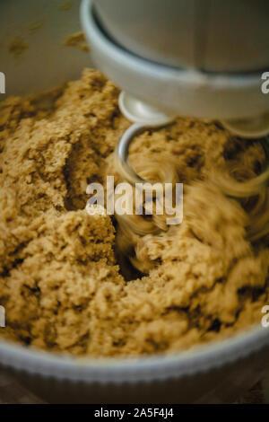 dark ginger cookie dough mixes in the mixer, close-up - Stock Photo