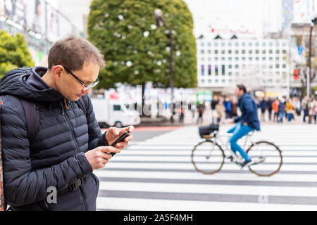 Tokyo, Japan famous Shibuya crossing and bicycle in background on crosswalk in downtown city with man tourist standing looking at directions on phone - Stock Photo