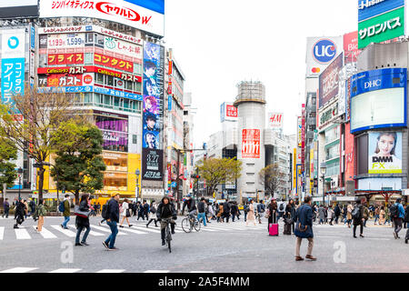 Tokyo, Japan - March 28, 2019: Famous Shibuya crossing crosswalk in downtown city with neon lights advertisements and traffic during day - Stock Photo