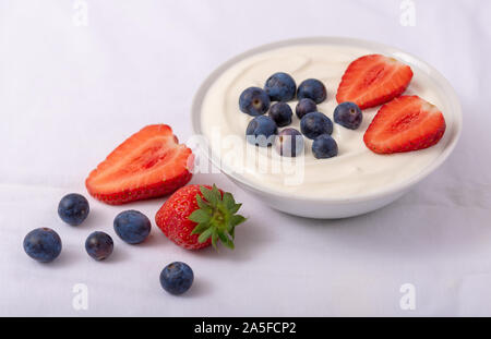 Yogurt in white bowl with strawberries and blueberries on white background. - Stock Photo