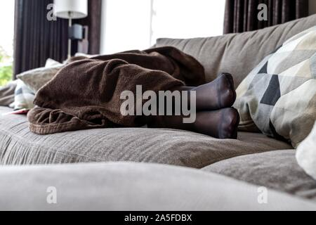 A potrait of a girls black pantyhose feet while she is sleeping in the couch in the living room under a brown cosy blanket. - Stock Photo