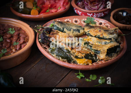 Chilles rellenos served in traditional mexican dishes, served with beans, pickles - Stock Photo