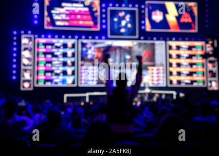 Blurred background of an esports event - Fan on a tribune at tournament's arena with hands raised - Stock Photo
