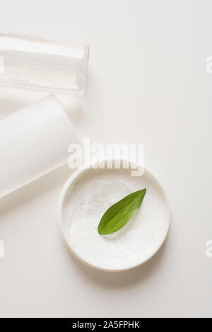 Means for skin care, rejuvenation and hydration of the face. Cream, micellar water and moisturizing lotion on a white background with a green leaf. The concept of self-care and care for the skin. - Stock Photo