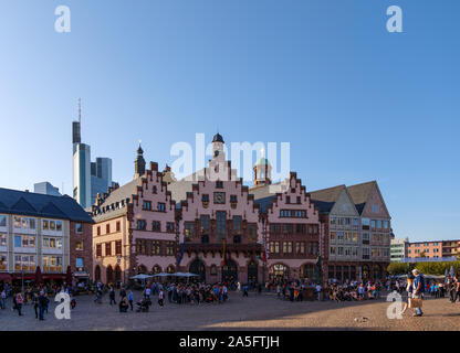 Outdoor sunny view of old town at Römerplatz, historical market square, surrounded with Römerberg, timber medieval German house, and city hall. - Stock Photo