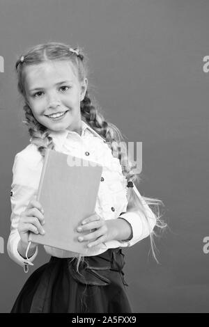 If knowledge you need, you must read. Cute little child holding book on red background, Small girl with book knowledge in hands. Knowledge day or September 1. Knowledge accumulation, copy space. - Stock Photo