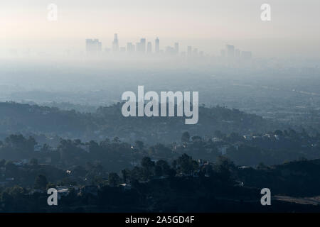 Thick hazy layer of smog and smoke from nearby brush fire clouding the view of downtown Los Angeles buildings in Southern California.   Shot from hill - Stock Photo