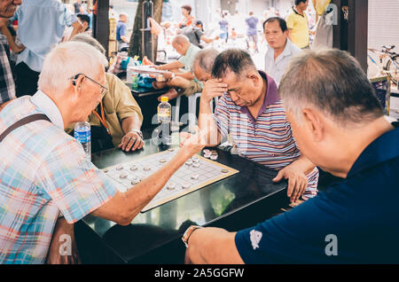 Singapore-09 JUN 2018:Chinese old man play traditional chess in the Singapore China town open plaza - Stock Photo