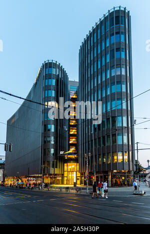 Berlin, Germany - July 27, 2019: Modern glass office building skyscraper in Friedrichstrasse area in Berlin Mitte against sky at sunset - Stock Photo