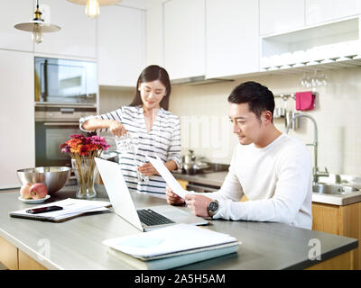 young asian man working at home using laptop computer while wife pouring a glass of water - Stock Photo