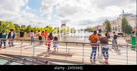 young people on Léopold-Sédar-Senghor footbridge with louvre and musee d´orsay in background - Stock Photo
