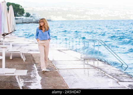 Full length shot of relaxed middle aged woman walking on the beach. - Stock Photo