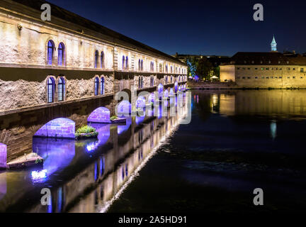 The Vauban Dam illuminated at night in Strasbourg, France, and the Commanderie Saint-Jean building which houses the National School of Administration. - Stock Photo