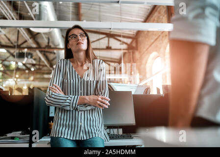 Working day. Young woman in casual wear keeping arms crossed and thinking about something while spending time in the office - Stock Photo