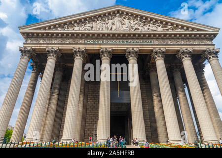 Low-angel shot of the La Madeleine church with its lovely portico front in Paris. The Corinthian columns and the pediment sculpture of the Last... - Stock Photo