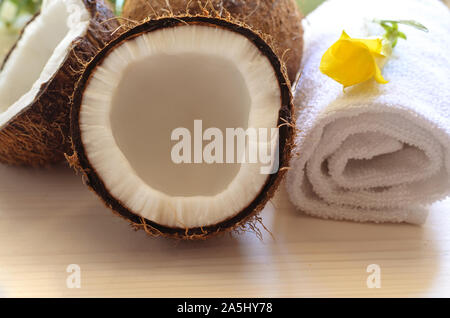 Coconut,  white towel and tropical flower on wooden background. Wellness or spa relax concept. - Stock Photo