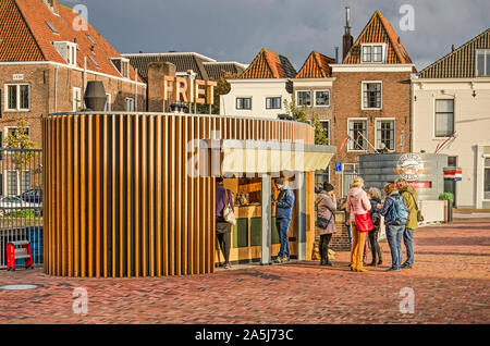 Middelburg, The Netherlands, October 9, 2019: modern chip shop with oval floor plan and wooden facade, with traditional canal houses in the background - Stock Photo