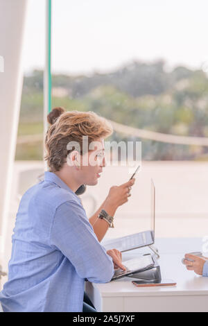 Profile of cute blond boy looking straight ahead wearing a light blue shirt with unfocused background. - Stock Photo