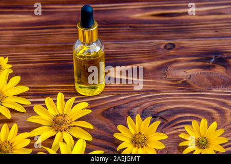 yellow flowers and cosmetic oil in a bottle on wooden background - Stock Photo