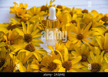 yellow flowers and white cosmetic cream in a bottle on a wooden light background - Stock Photo