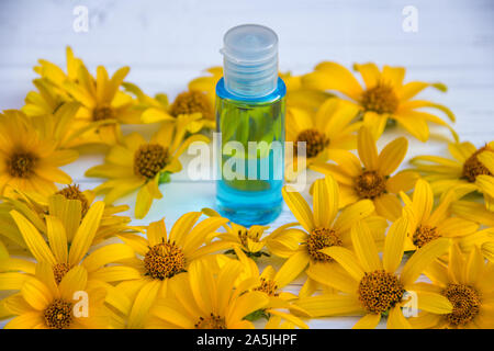 yellow flowers and blue tonic in a bottle on a wooden light background - Stock Photo