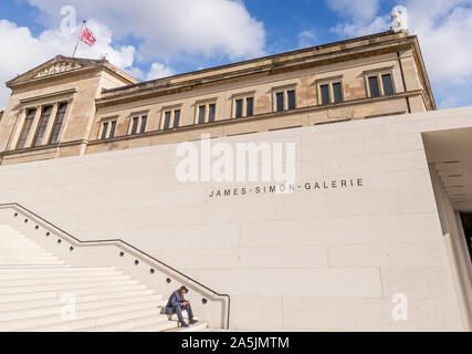 Elegant man using his mobile phone sitting on the steps of the James-Simon-Galerie in Berlin, Germany - Stock Photo