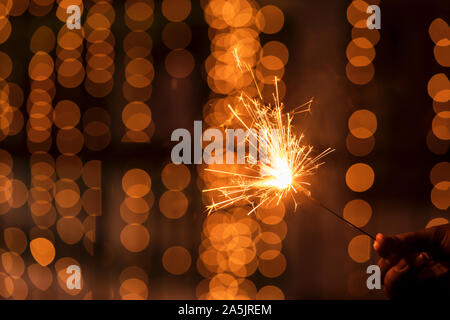 Abstract Sparkelrs background with light yellow bokeh, bright festive Diwali, Christmas, Happy New Year background stock image. Man Holding Sparkler. - Stock Photo