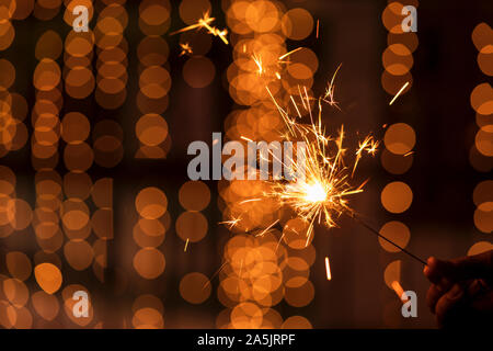 Happy Diwali - Lighting a Sparkler. Model holding sparkler concept for festive season Diwali, dhanteras, Christmas, New year celebrations background. - Stock Photo