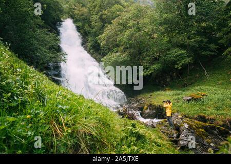 Gudvangen-Naeroyfjorden, Norway. Waterfall Tuftofossen In Spring. Natural Norwegian Landmark. Young Caucasian Woman Lady Tourist Traveler Photographer - Stock Photo