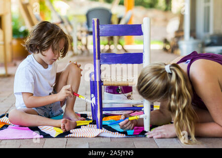 5 year old boy painting children's chair on porch with his sister