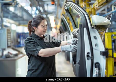 Female apprentice engineer assembling car doors in car factory - Stock Photo