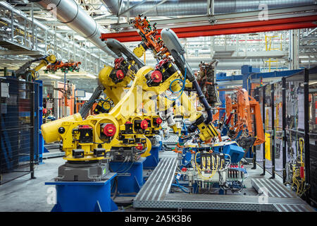 Robots with car parts in car factory - Stock Photo