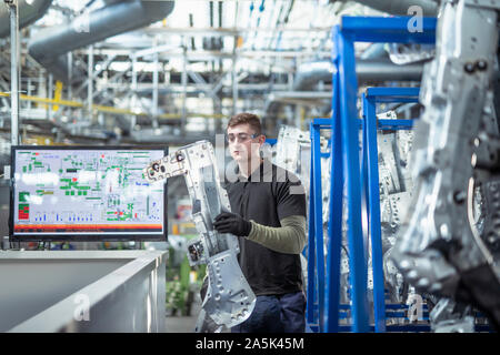 Male apprentice engineer inspecting parts in car factory - Stock Photo