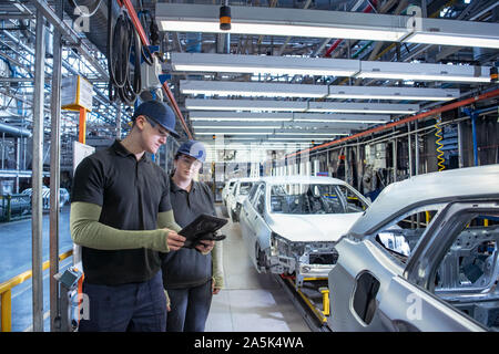 Apprentices inspecting cars on production line in car factory - Stock Photo