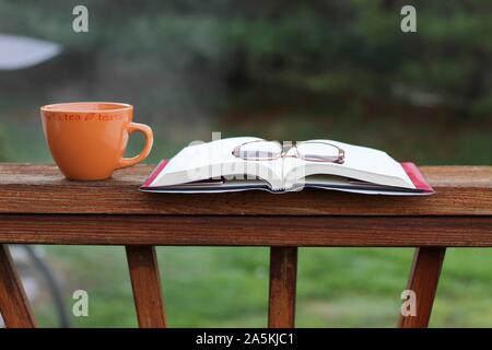 A pair of reading glasses on top of a book and a cup of tea outside on a deck - Stock Photo